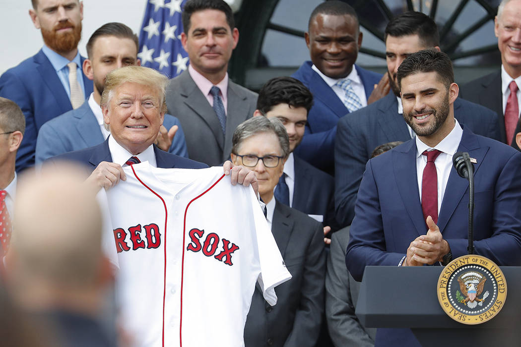 President Donald Trump, left, holds a team jersey that was presented to him by outfielder J.D. ...