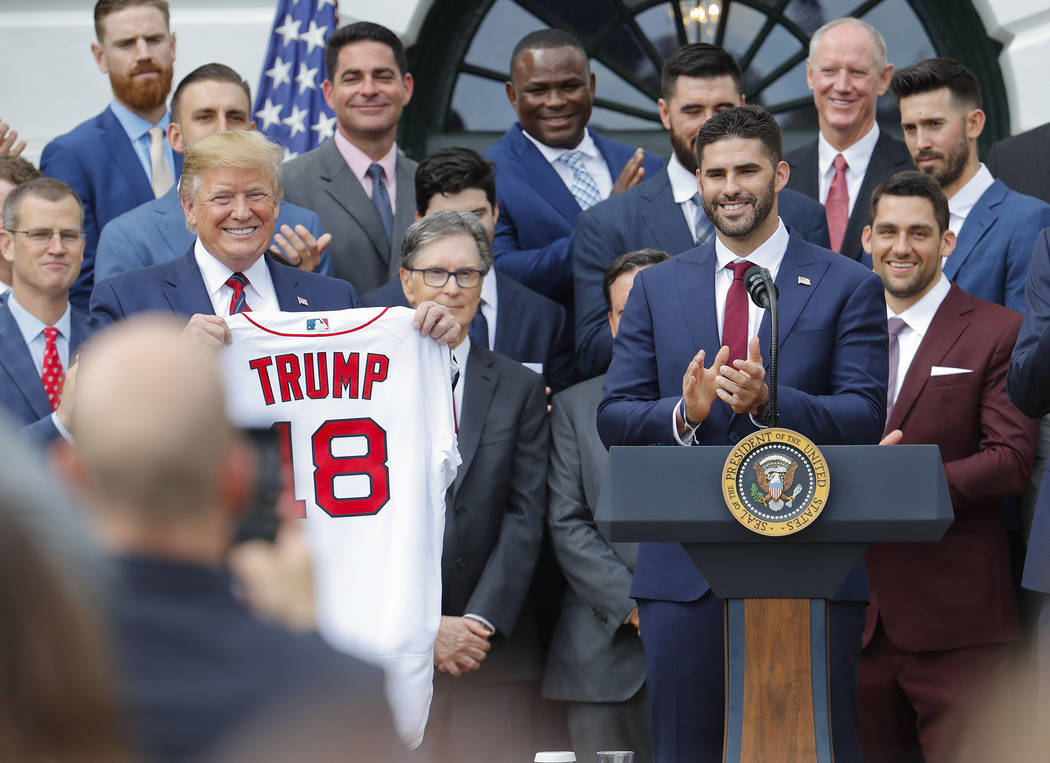 President Donald Trump, left, holds up a team jersey that was presented to him by outfielder J. ...
