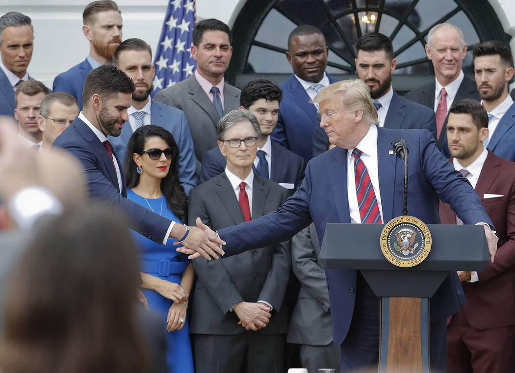 President Donald Trump, right, reaches over to shake hands with outfielder J.D. Martinez, left, ...