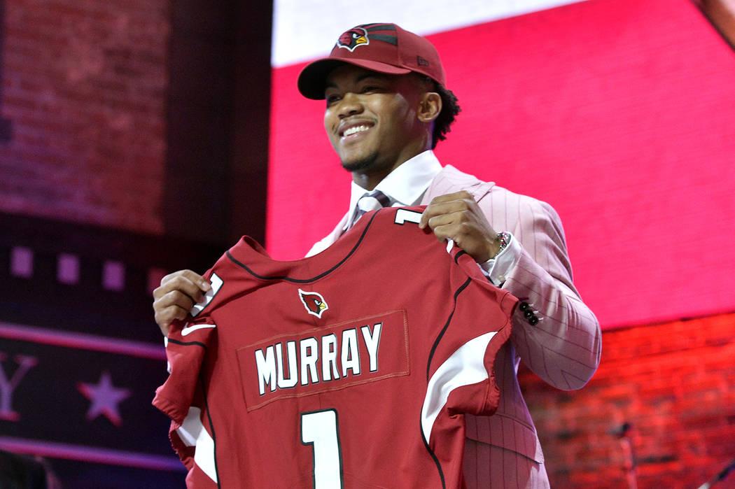Oklahoma quarterback Kyler Murray holds his up a jersey after the Arizona Cardinals selected Mu ...