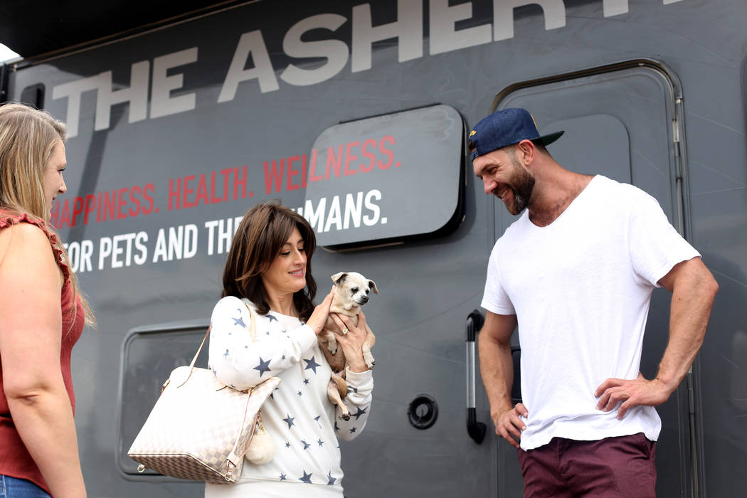 Paula Ditusa holds Queen as Lee Asher talks to Renne Babiracki outside The Asher House RV in th ...