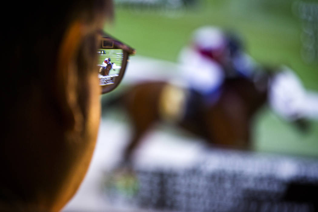 A man watches a horse race on a tv monitor in the William Hill Race & Sports Book at the Plaza ...
