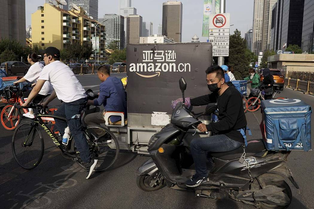 In this Wednesday, May 8, 2019, photo, a delivery man bearing U.S. commerce giant Amazon's bran ...