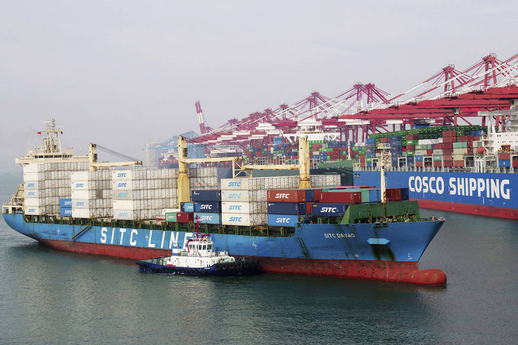 In this Wednesday, May 8, 2019, photo, a barge pushes a container ship to the dockyard in Qingd ...