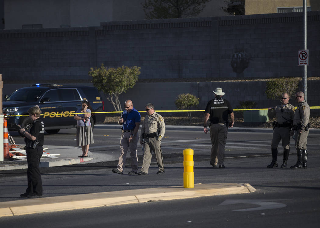 Law enforcement investigate a car accident at South Fort Apache Road and West Arby Avenue that ...