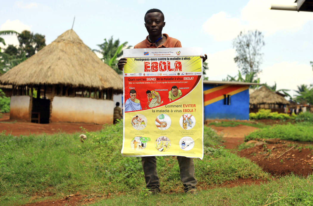 FILE - In this Wednesday, Aug 8, 2018 file photo, a man displays an Ebola information leaflet f ...