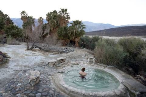 A visitor relaxes in the hot springs of Saline Valley at Death Valley National Park. (J. Emilio ...