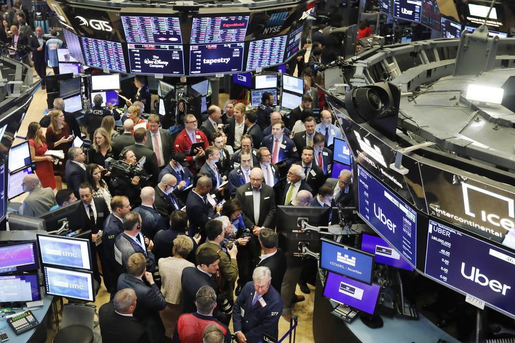 Stock traders gather around the post where Uber shares will begin trading during the company's ...