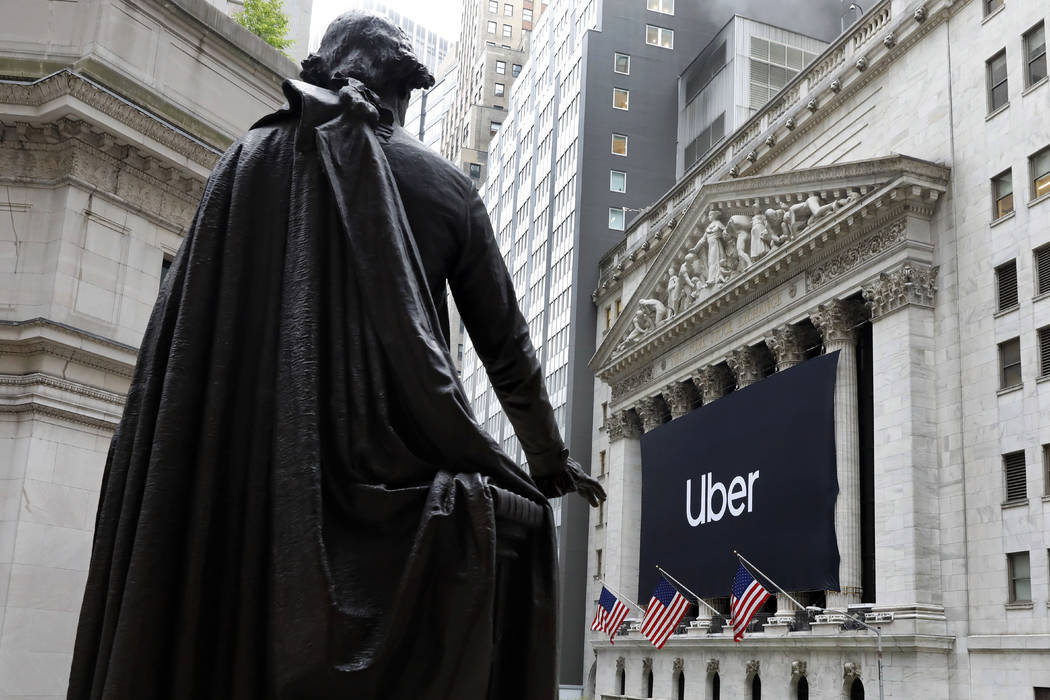 The statue of George Washington, on the steps of Federal Hall, overlooks the Uber banner hangin ...