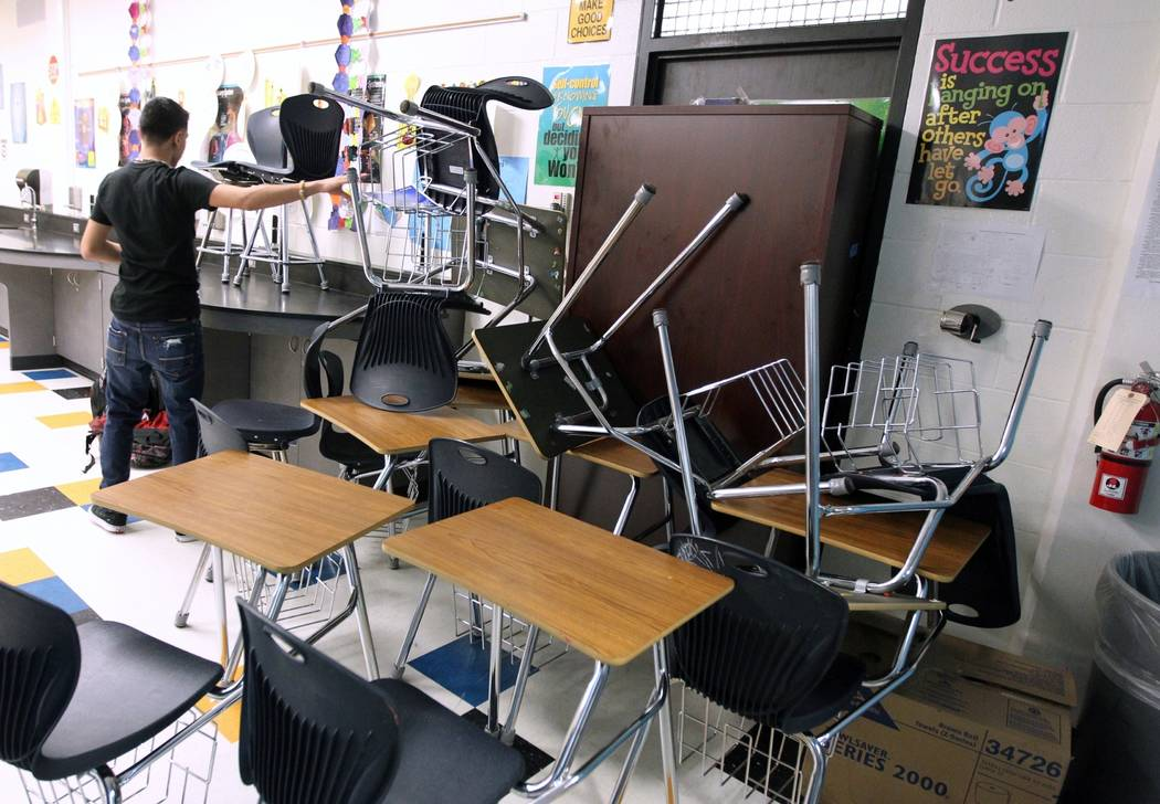 FILE - In this Jan. 22, 2013, file photo, a student helps block the classroom door with furnitu ...