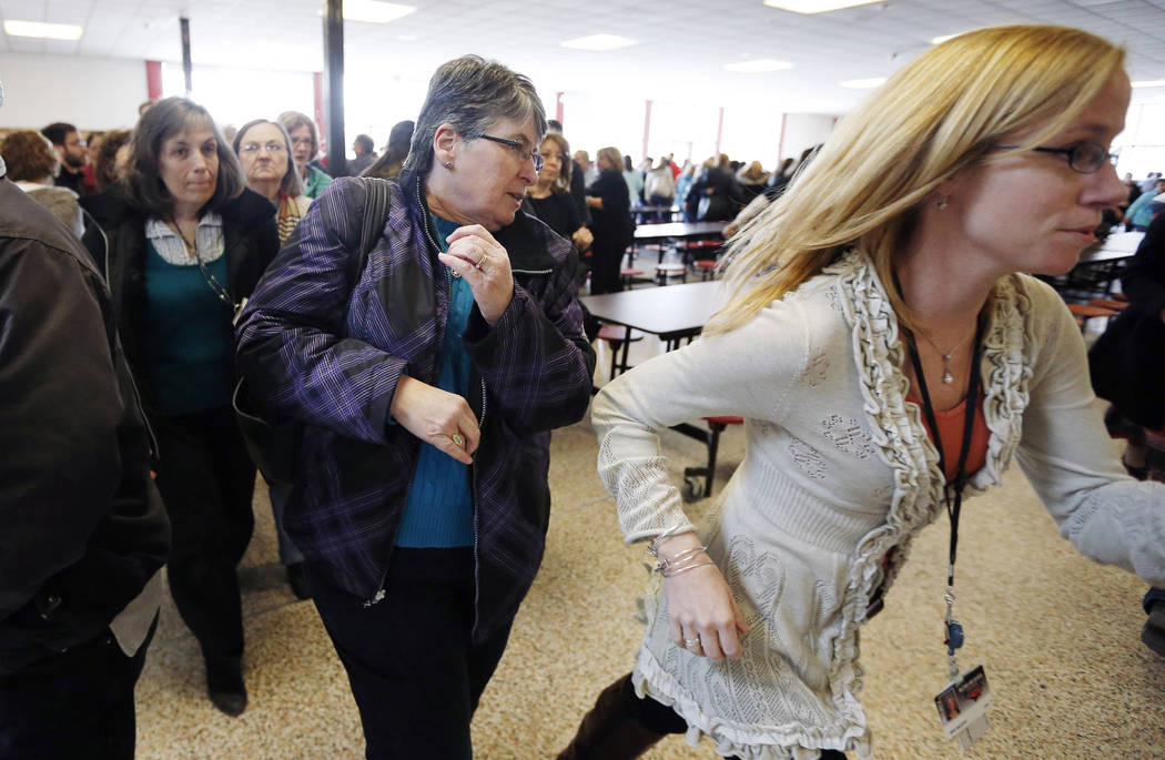 Participants rush out of the cafeteria after hearing gun shots during a lockdown exercise March ...