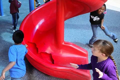 Students run around a broken slide in the playground at Helen Smith Elementary School in Las Ve ...