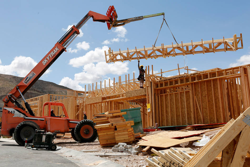 Workers construct houses near the corner of Mesa Park Drive and Hualapai Way in Summerlin, Frid ...