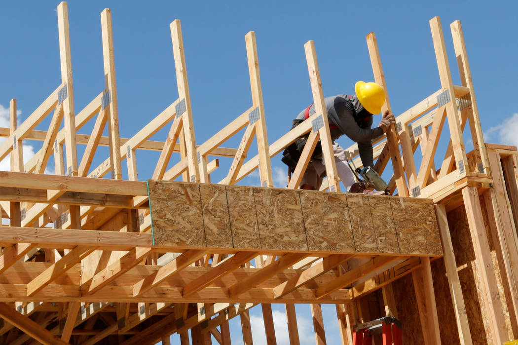 A worker constructs a house near the corner of Mesa Park Drive and Hualapai Way in Summerlin, F ...