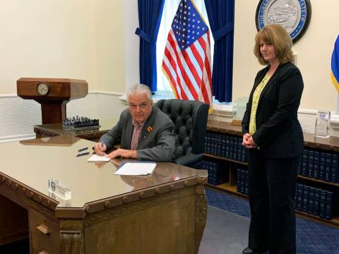 Gov. Steve Sisolak, left, checks the time as he signs Senate Bill 32, which increases transpare ...