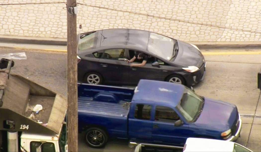 In this photo from video provided by FOX11 Los Angeles shows a man leaning out the window of a ...