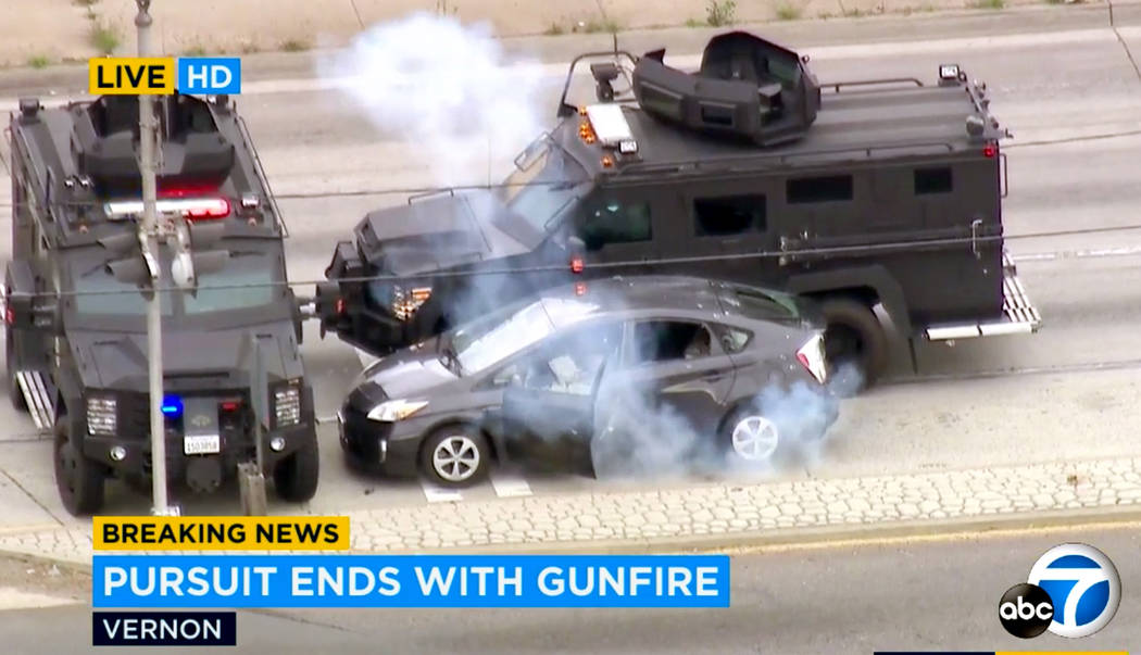 In this photo taken from video provided by KABC-TV, armored police vehicles block a car and dep ...