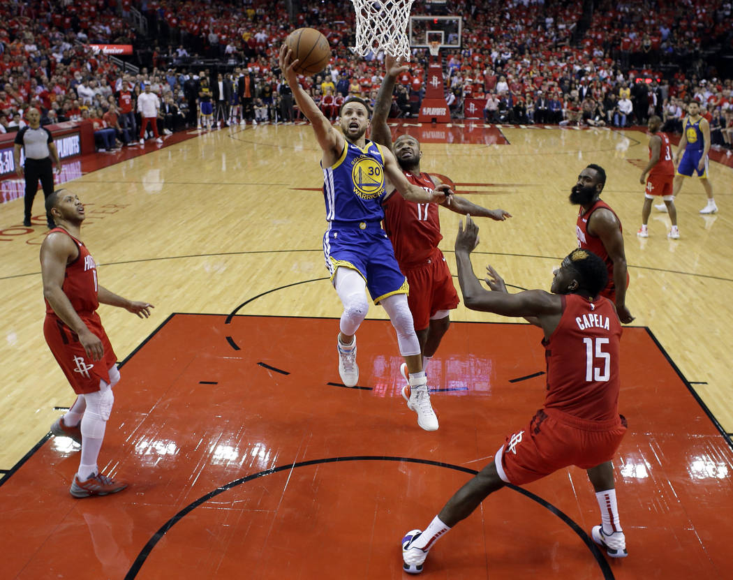 Golden State Warriors' Stephen Curry (30) goes up for a shot between Houston Rockets' Eric Gord ...