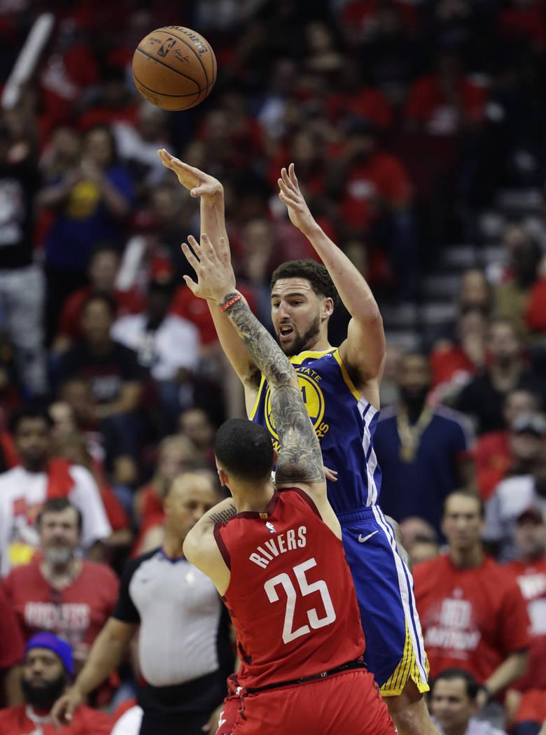 Golden State Warriors guard Klay Thompson (11) passes the ball over Houston Rockets guard Austi ...