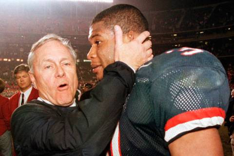In this Dec. 30, 1998, file photo, Arizona coach Dick Tomey, left, congratulates linebacker DaS ...