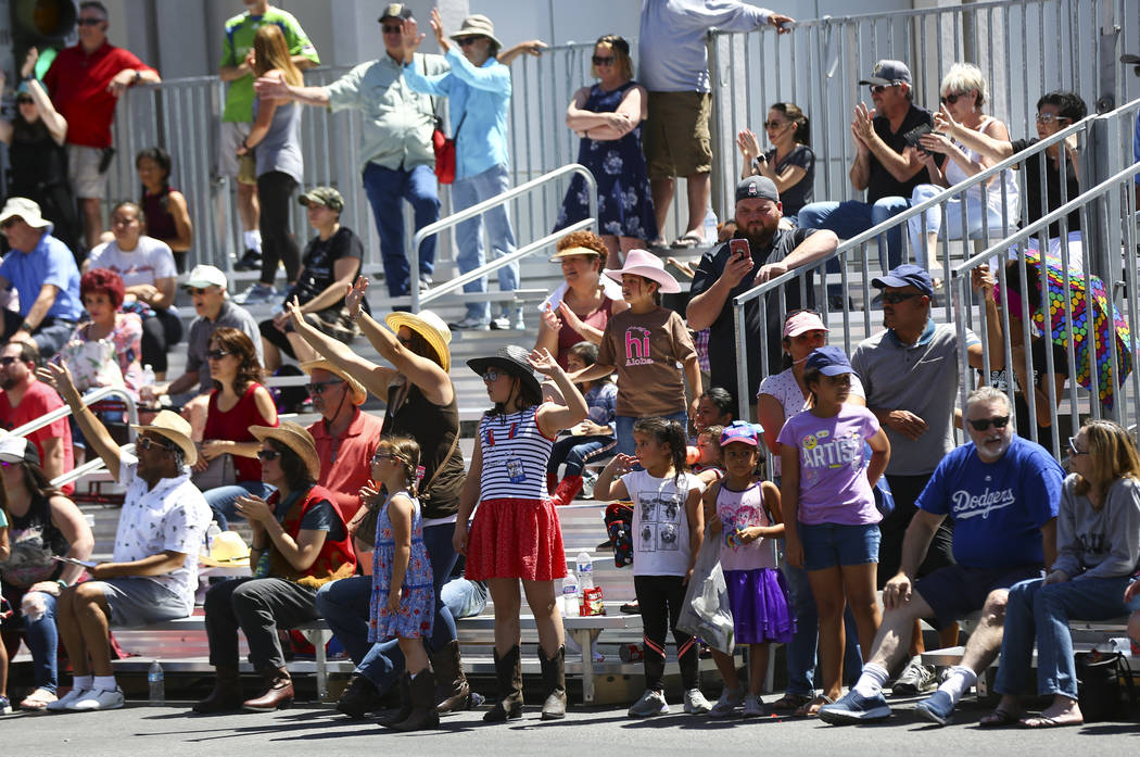 Attendees wave their hands as items are given out by LV.Net during the Helldorado Parade along ...