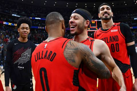 From front, Portland Trail Blazers guard Damian Lillard celebrates with guard Seth Curry and ce ...