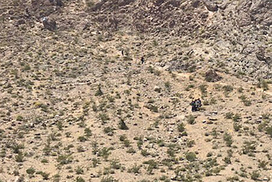 Rescuers carry a sick hiker down Lone Mountain in Las Vegas on Sunday, May 12, 2019. (Las Vegas ...