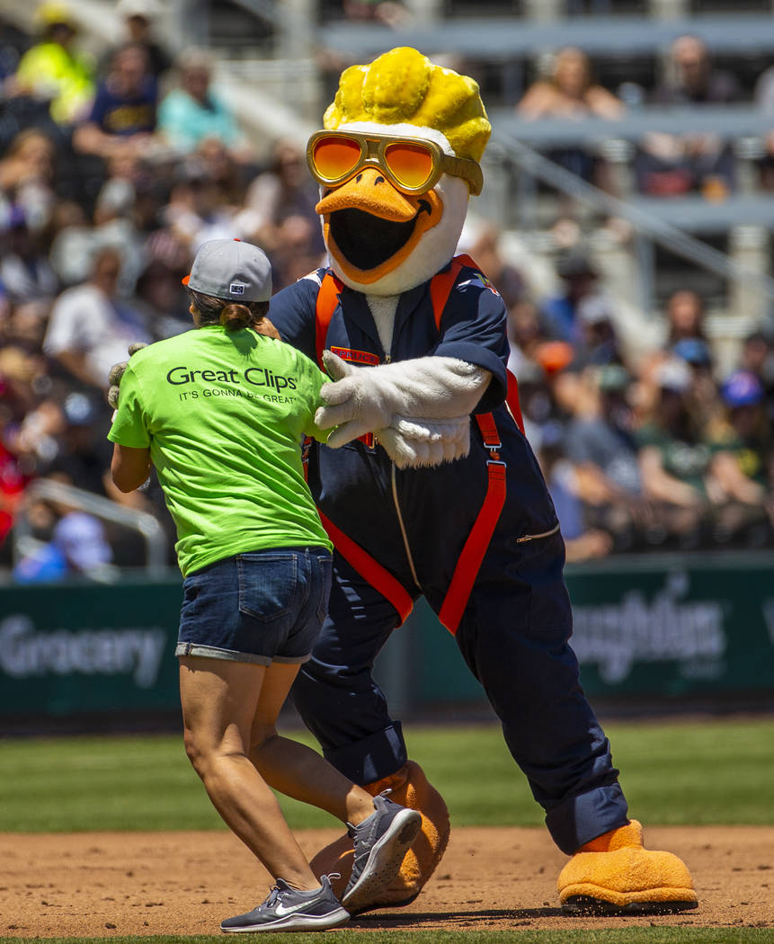 Puddles the Duck attempts to slow down Erica Haskin as they race around the bases while the Avi ...