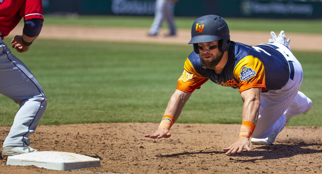 The Aviators Nick Martini (38) dives back to first base during a game versus the Tacoma Rainier ...