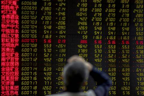 A man rubs his forehead as he monitors stock prices at a brokerage house in Beijing, Monday, Ma ...