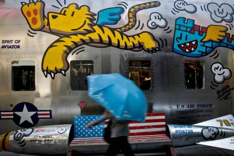 A woman walks by a bench painted with an American flag outside a fashion boutique selling U.S. ...