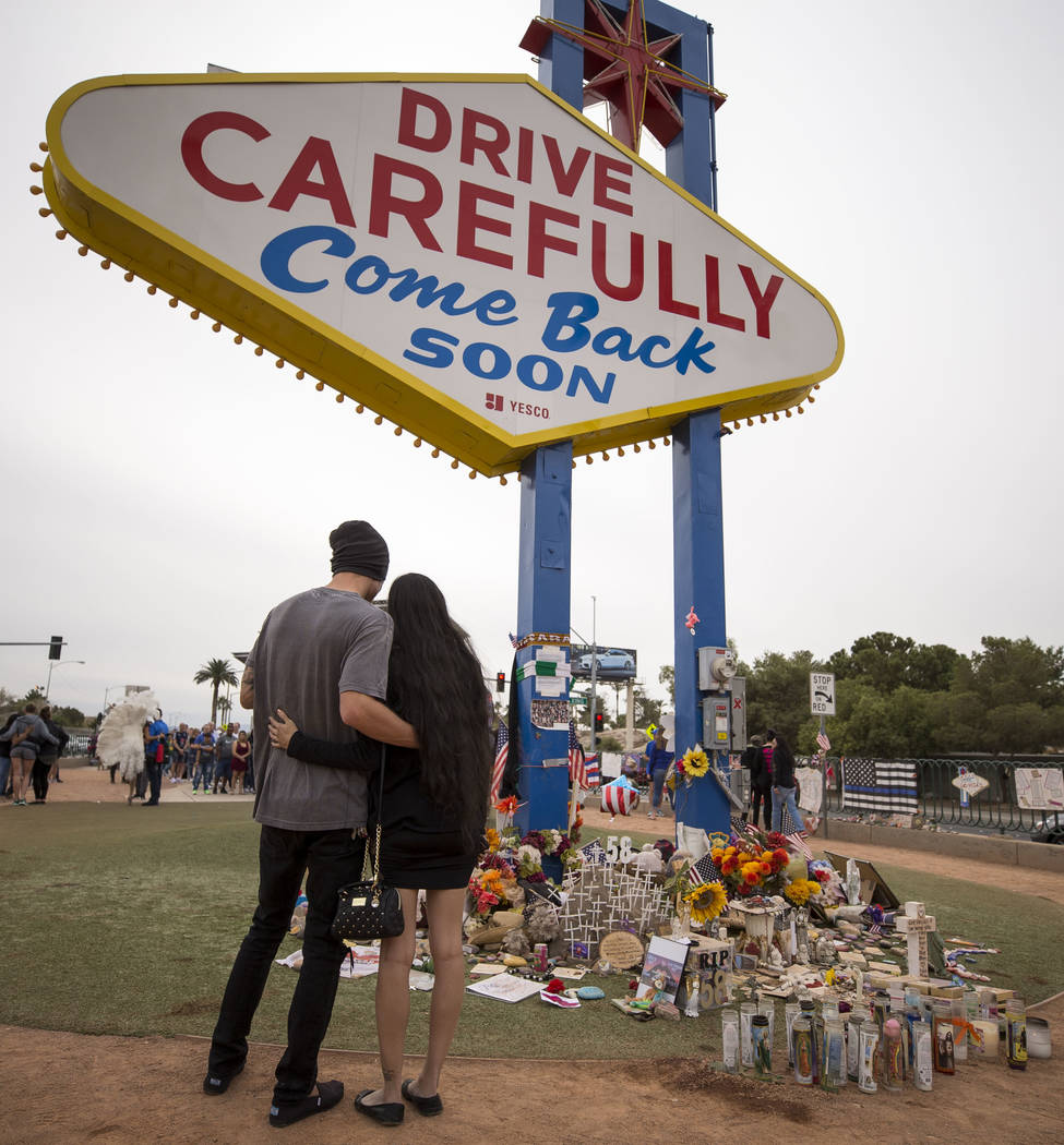 """A couple embraces as they visit a memorial for the Route 91 Harvest shooting victims at the """"We ..."""
