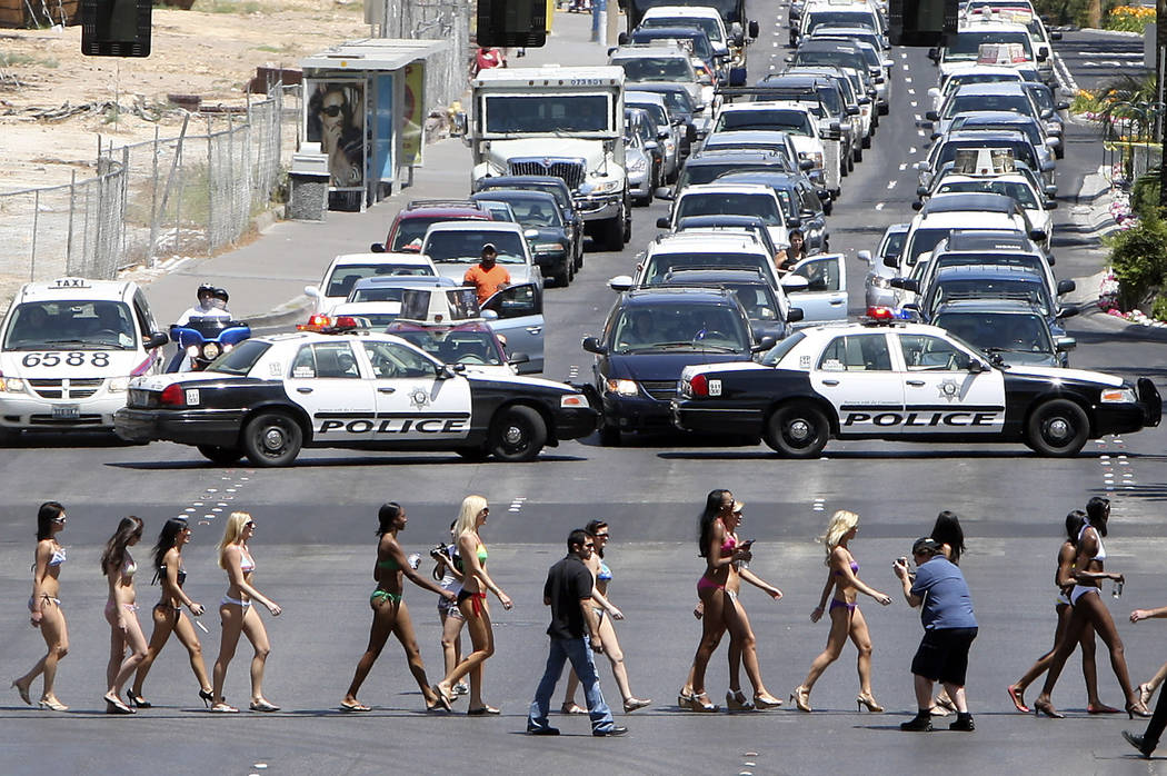 Bikini-clad women stop traffic with a little aid from the Las Vegas police as they form the wor ...