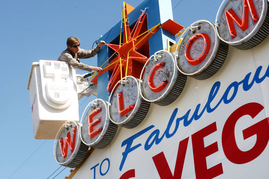 """YESCO sign serviceman Kenny West examines the neon on the iconic """"Welcome to Fabulous Las Vegas ..."""
