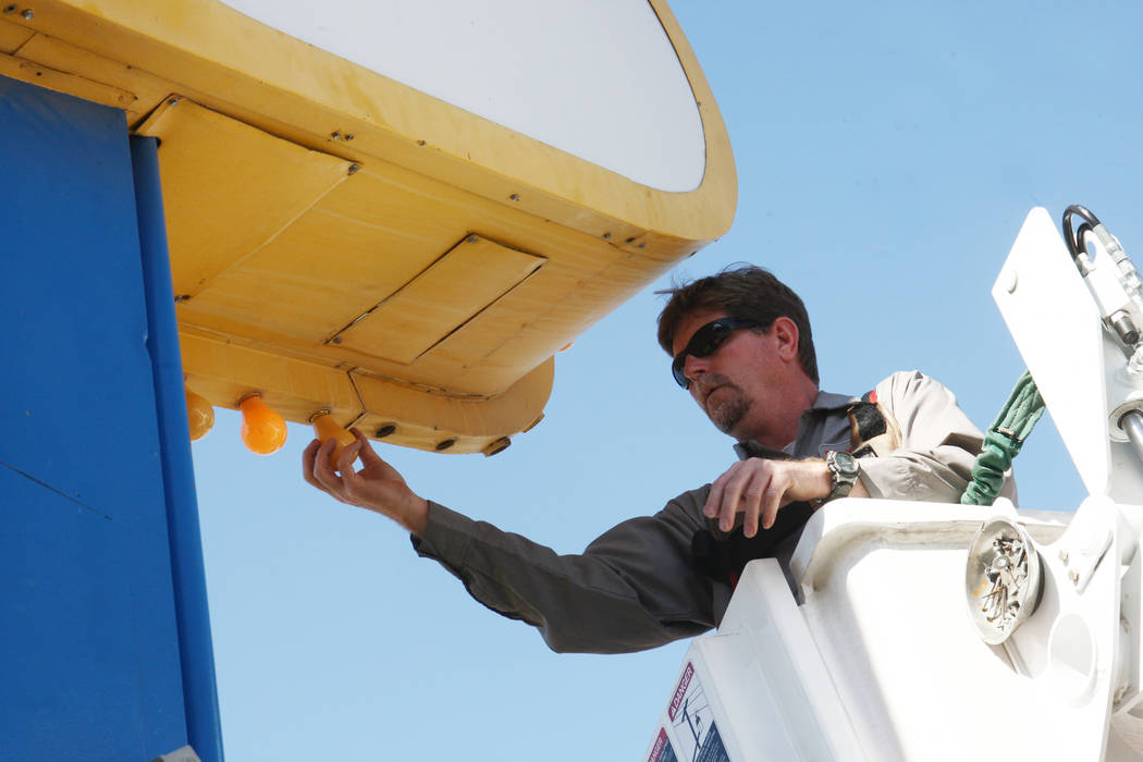 """YESCO sign serviceman Kenny West changes out the bulbs on the iconic """"Welcome to Fabulous Las V ..."""