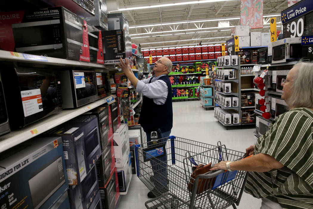 Assistant Manager James Hutchinson helps Diane Campbell of Henderson with a purchase at Walmart ...