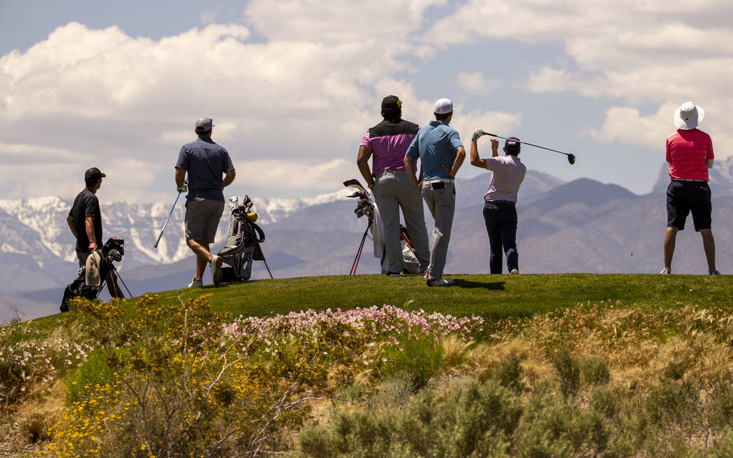 Golfers tee off with snow on Mt. Charleston as a background during a PGA US Open qualifying rou ...