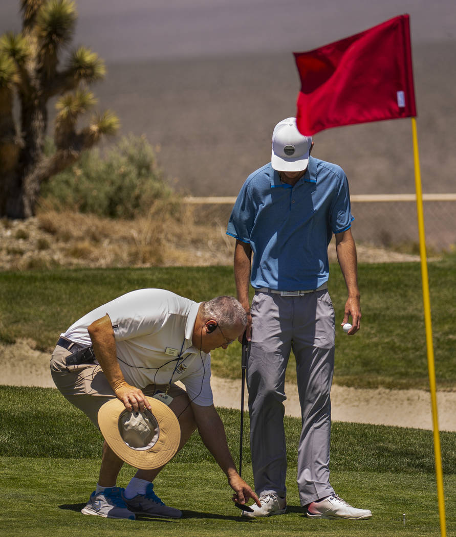 Time Quinn with the rules team instructs golfer Van Thomas on ball placement as his was in a di ...