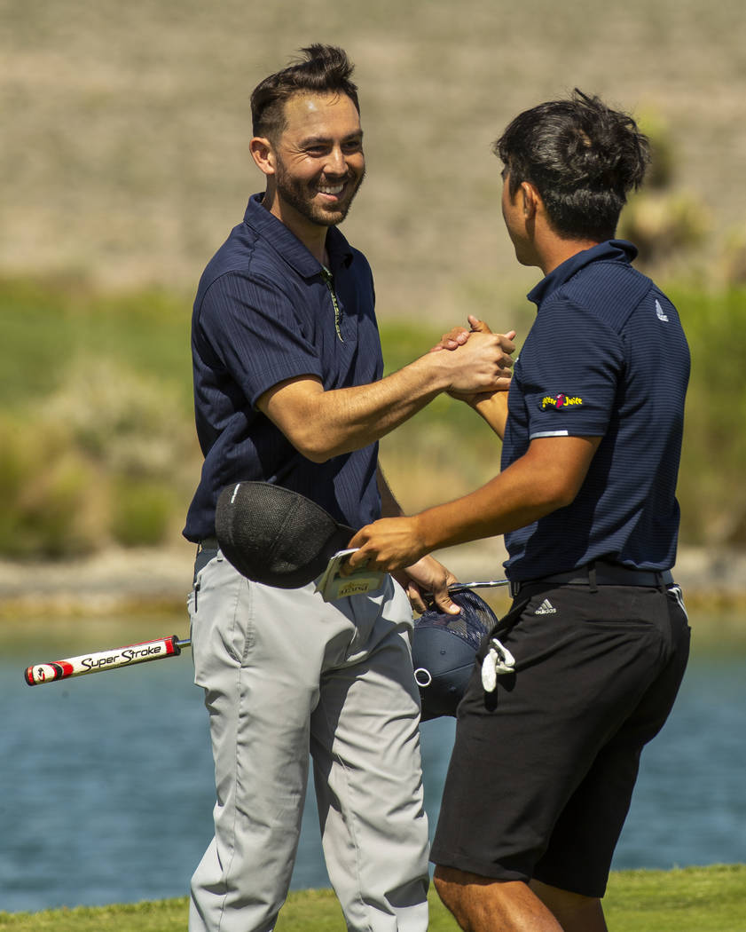 Golfers Brett Kanda and Alexander Kang celebrate their qualifying score on the 18th hole during ...