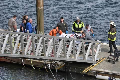Emergency response crews transport an injured passenger to an ambulance at the George Inlet Lod ...