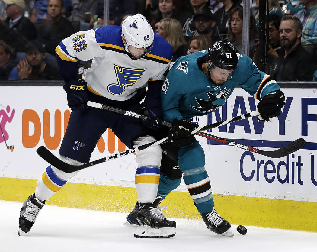 St. Louis Blues' Ivan Barbashev, left, and San Jose Sharks' Justin Braun fight for the puck dur ...
