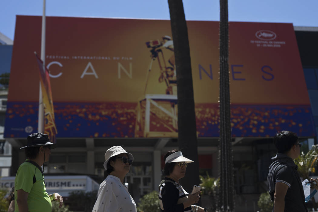 Festival goers walk by the Palais des festivals during the 72nd international film festival, Ca ...