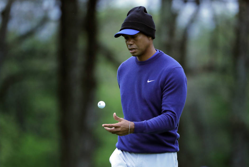 Tiger Woods flips his ball as he walks along the ninth green during a practice round for the PG ...