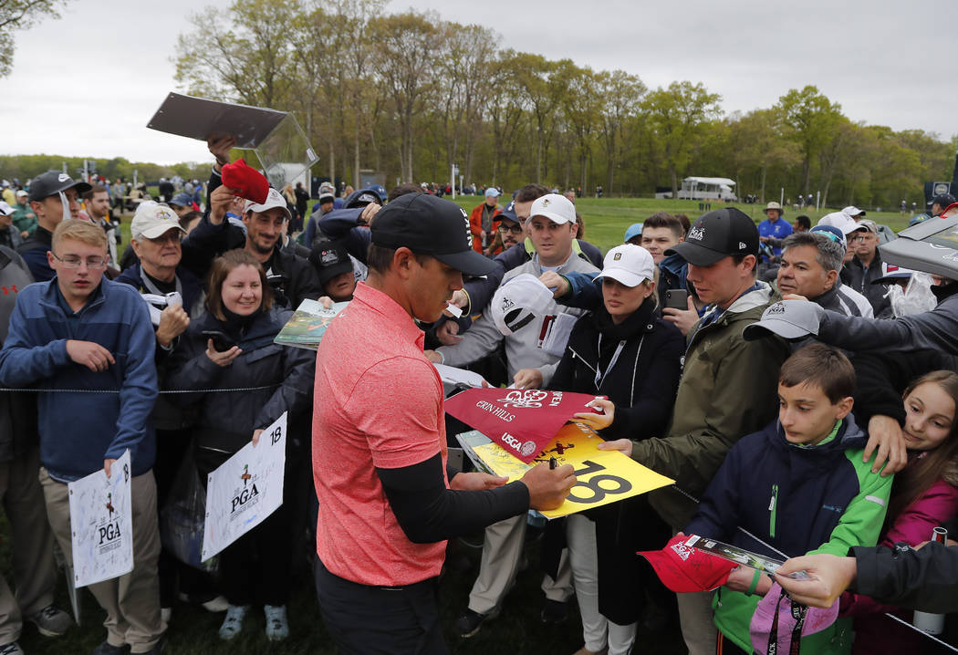 Brooks Koepka signs autographs for fans after a practice round at the PGA Championship golf tou ...