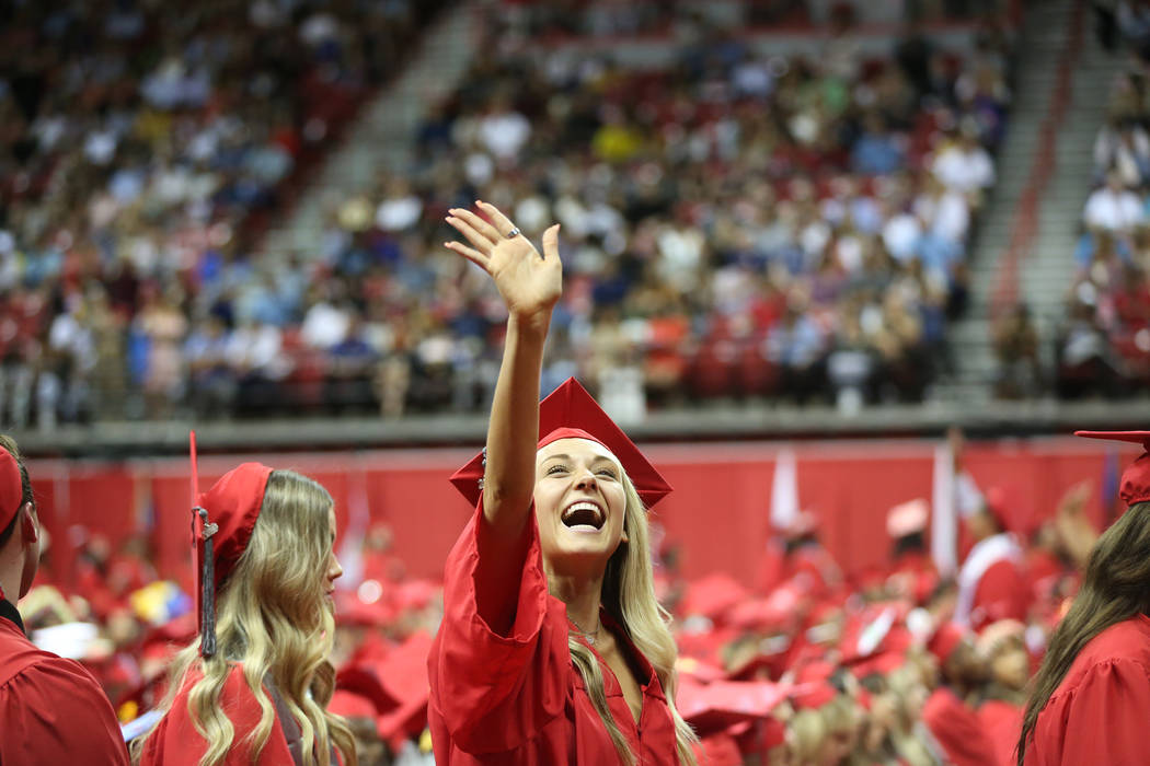 Communications major Alexandra Brianna Grady waves as she gets ready to walk the stage during t ...