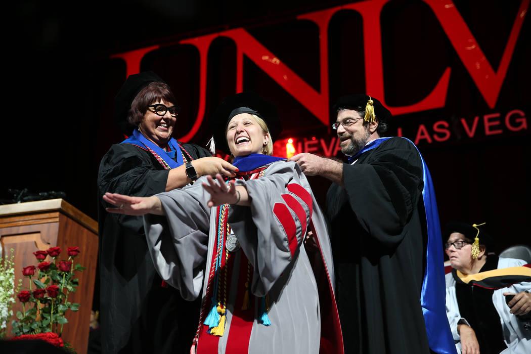 Sociology doctorate graduate Valarie Burke is hooded by Kate Korgan, left, dean of the graduate ...