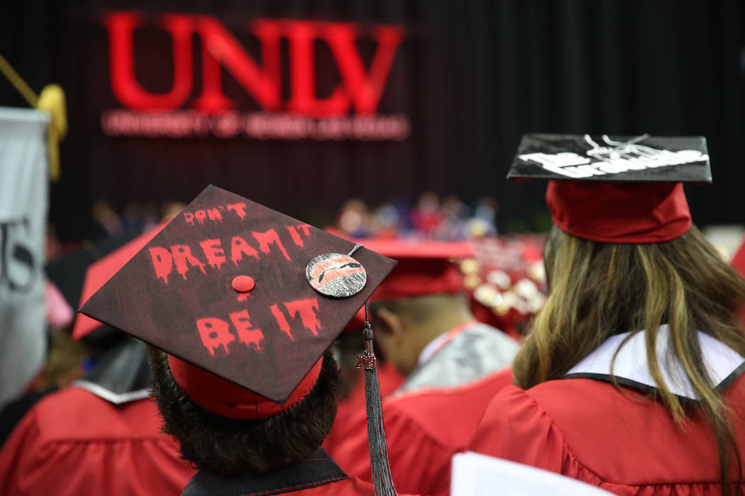 Graduates attend the UNLV commencement ceremony at the Thomas & Mack Center in Las Vegas, S ...