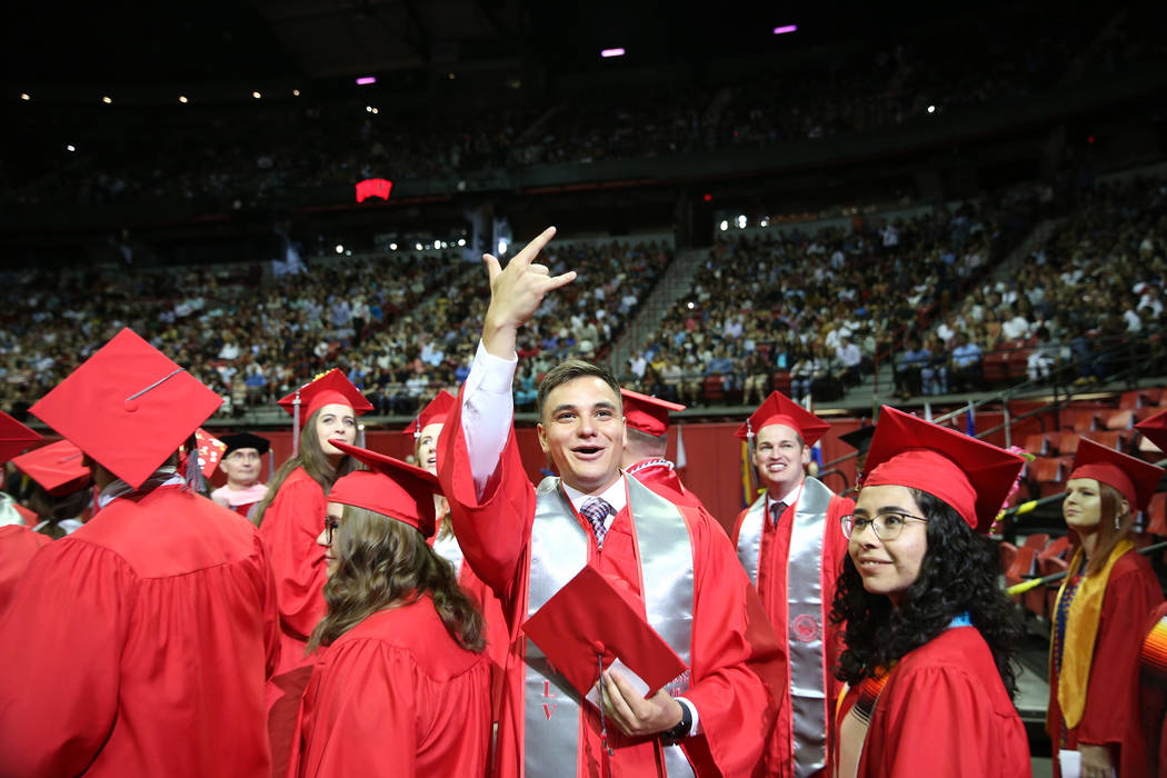 History major graduate Joseph Sanchez, center, 24, gestures to people in the crowd during the U ...