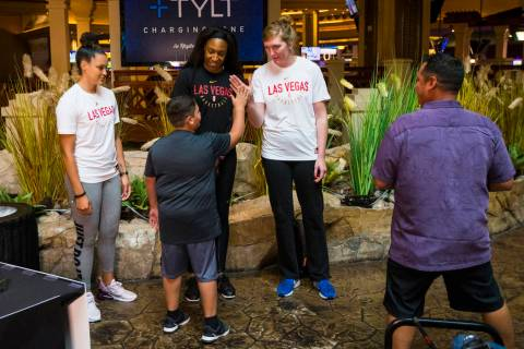 Braeden Sada, 11, high-fives Las Vegas Aces player Carolyn Swords, right, as players Kayla McBr ...