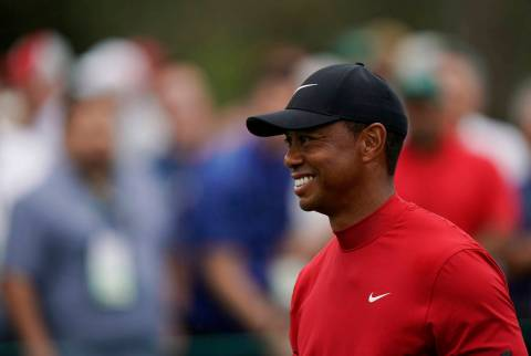 Tiger Woods smiles as he walks off the seventh tee during the final round for the Masters golf ...